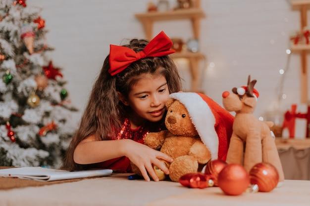 Une petite fille avec son ours préféré dans le chapeau du père noël fait un vœu de noël et écrit une lettre au père noël