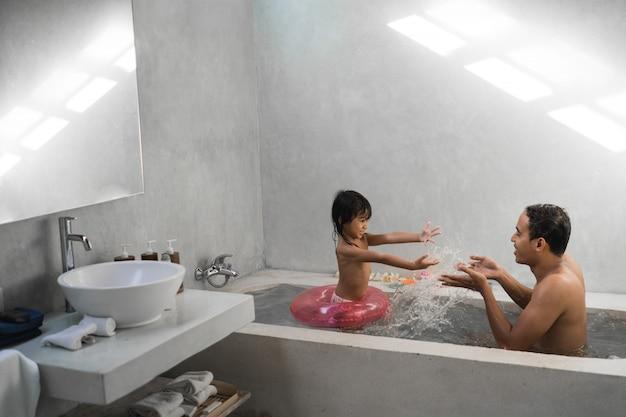 Petite fille avec son père jouant de l'eau sur la baignoire