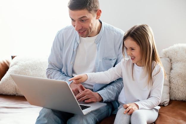 Petite fille et son père passent du temps ensemble sur un ordinateur portable