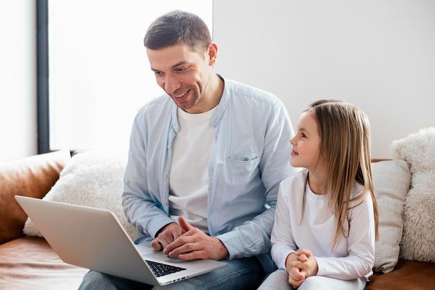 Petite fille et son père passent du temps sur un ordinateur portable