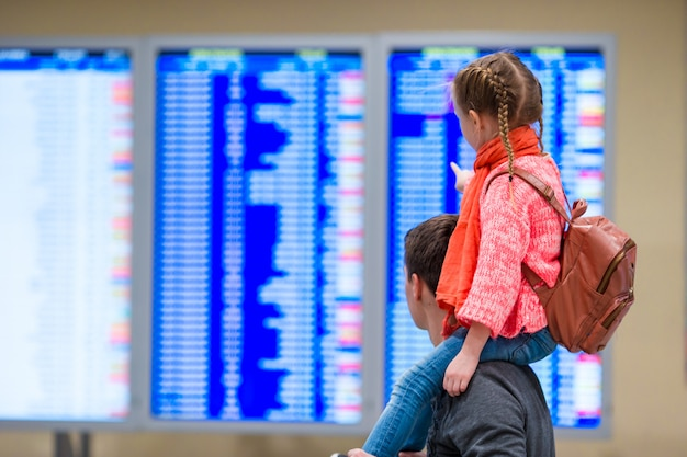 Petite fille avec son père à la recherche d'informations de vol à l'aéroport