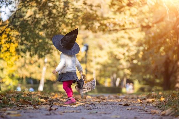 Petite fille sorcière marche dans la forêt d'automne avec un panier de feuilles.