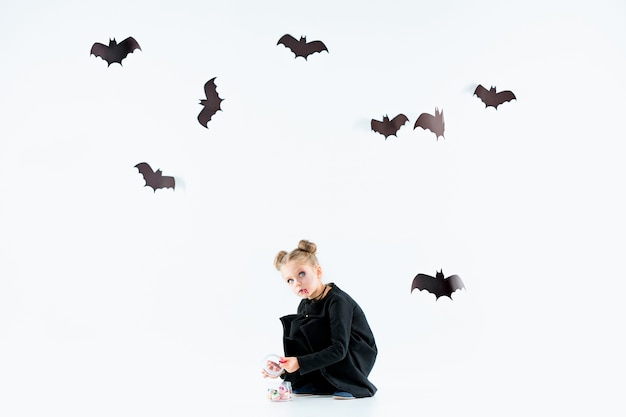 Petite fille sorcière en robe longue noire et accessoires magiques. halloween.
