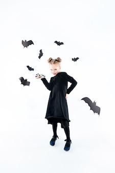 Petite fille sorcière en robe longue noire et accessoires magiques. halloween
