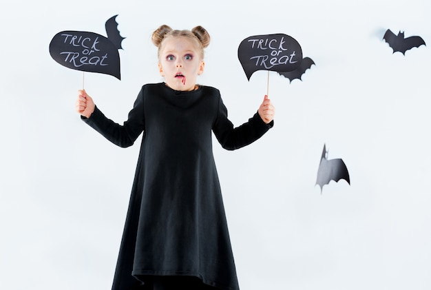 Petite fille sorcière en robe longue noire et accessoires magiques.