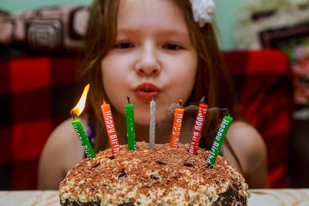 Petite fille soufflant des bougies d'anniversaire