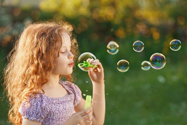 Petite fille soufflant des bulles de savon au printemps en plein air.