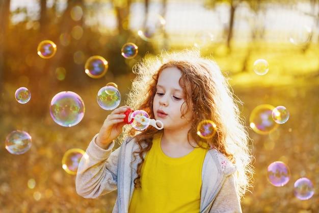 Une petite fille soufflant des bulles de savon dans un parc en automne