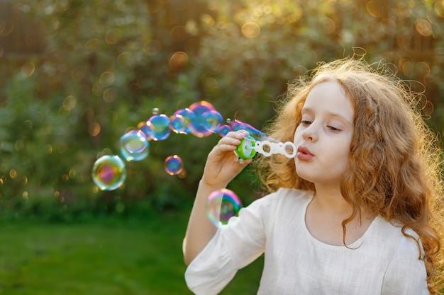 Petite fille soufflant des bulles de savon dans le parc de l'été.
