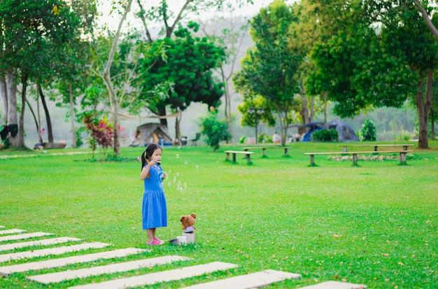Petite fille soufflant des bulles de savon dans le parc