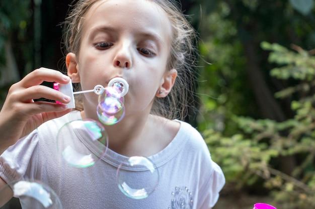 Petite fille soufflant des bulles de savon