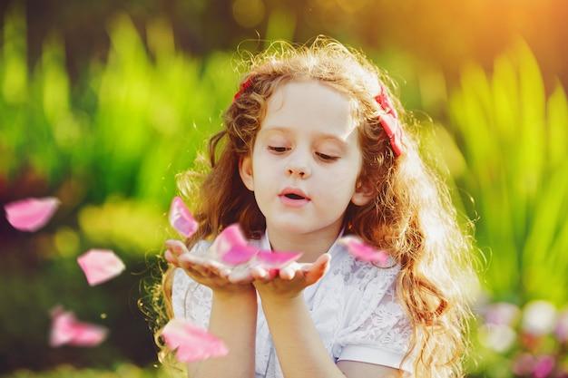 Petite fille soufflant des pétales de rose de ses mains.