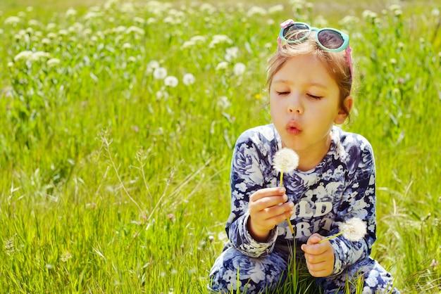 Petite fille soufflant des pissenlits sur la prairie au printemps
