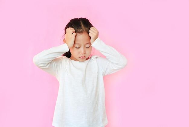 Petite fille souffrant de maux de tête sur fond rose