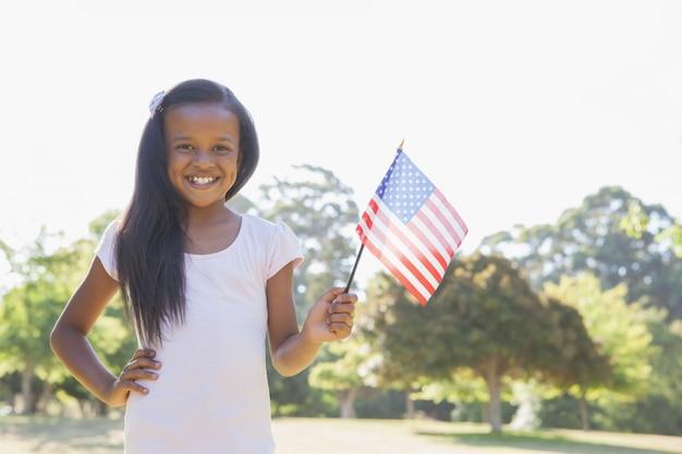 Petite fille, souriant à la caméra, agitant le drapeau américain