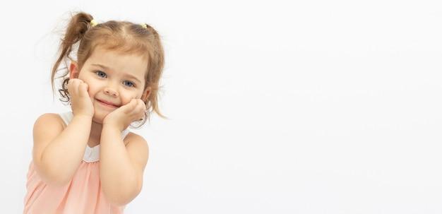 Une petite fille souriante de 2 ans a pressé ses paumes contre son visage. isolé sur fond blanc. espace pour le texte.