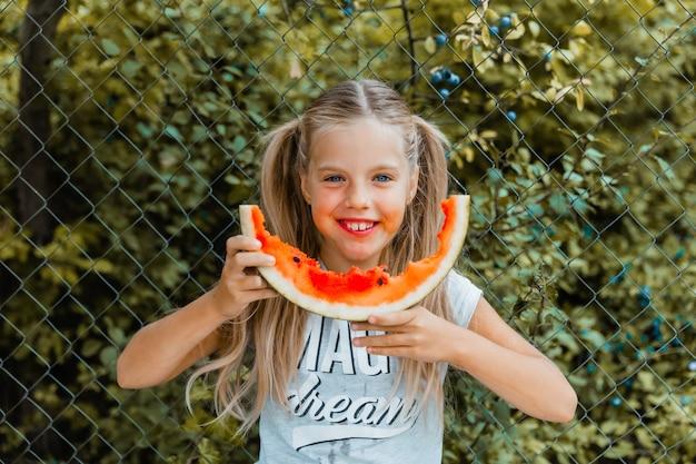 Petite fille souriante aux yeux bleus mangeant un morceau de pastèque à l'extérieur.