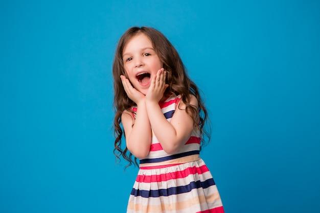 Petite fille souriante sur bleu