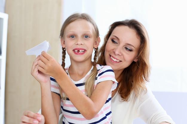 Petite fille souriante blonde faire un avion en papier