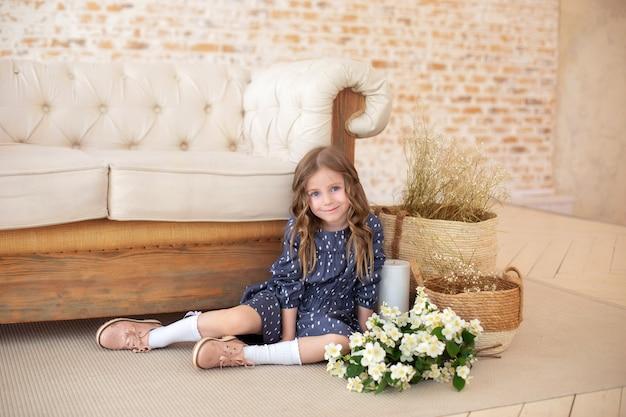Petite fille souriante avec un bouquet de fleurs de jasmin dans le salon enfant avec un bouquet de fleurs pour maman