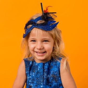 Petite fille souriante en costume avec masque