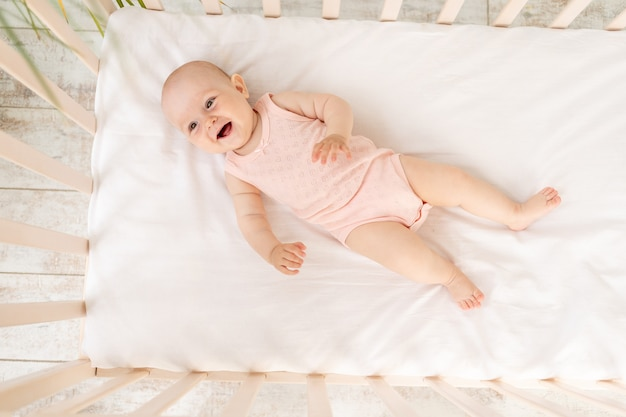 Petite fille souriante dans un berceau dans un body rose six mois sur un lit en coton blanc en riant, vue de dessus