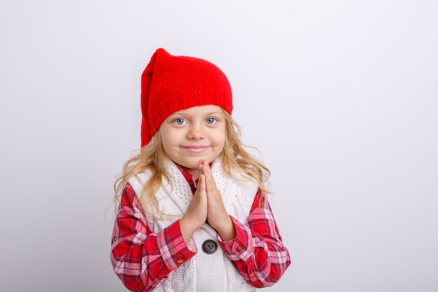 Une petite fille souriante dans un bonnet de noel croisa les bras devant elle, complètement isolée sur fond blanc