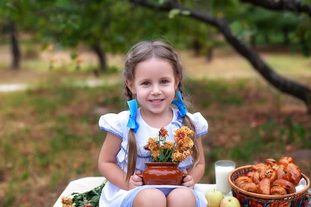 Petite fille souriante avec deux nattes sur la tête tenant des fleurs avec de la nourriture en pique-nique dans le jardin