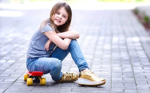 Une petite fille souriante est assise sur une planche à roulettes dans la rue en été