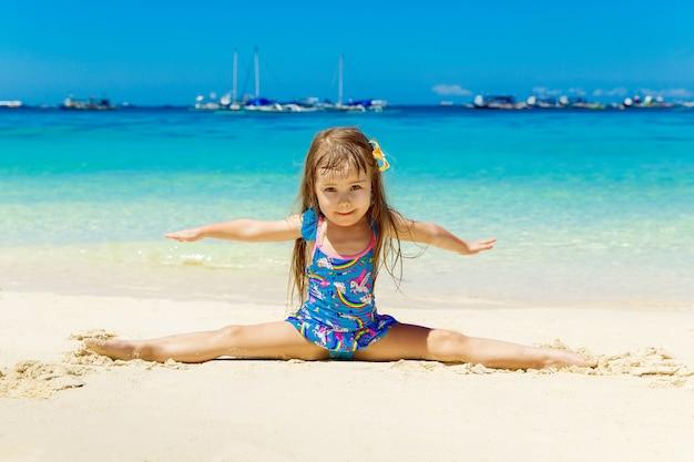Petite fille souriante faisant des divisions de gymnastique sur une plage tropicale de sable