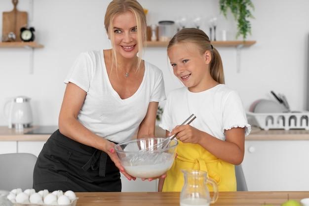 Petite fille souriante et femme faisant la cuisine