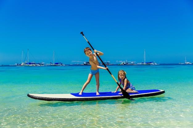 Petite fille souriante et garçon s'amusant sur un paddleboard dans la mer tropicale