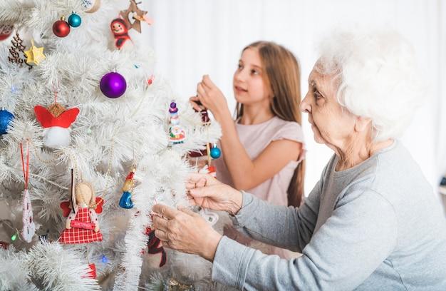 Petite-fille souriante avec grand-mère décoration arbre de noël fantaisie