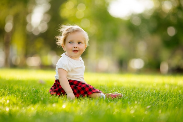 Petite fille souriante sur l'herbe verte
