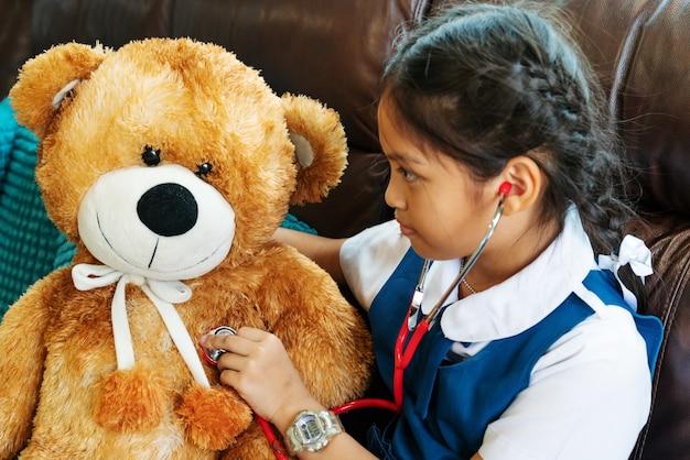 Petite fille souriante et jouant au docteur avec l'ours brun et le stéthoscope. kid et soins de santé