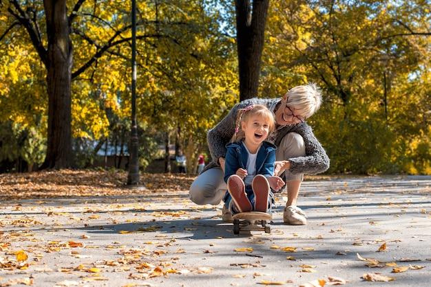 Petite-fille souriante jouant avec son grand-père dans le parc