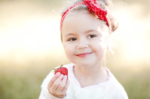 Petite fille souriante mangeant des fraises fraîches à l'extérieur
