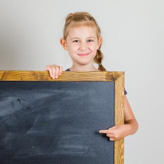 Petite fille souriante et pointant sur le tableau noir en vue de face de t-shirt.