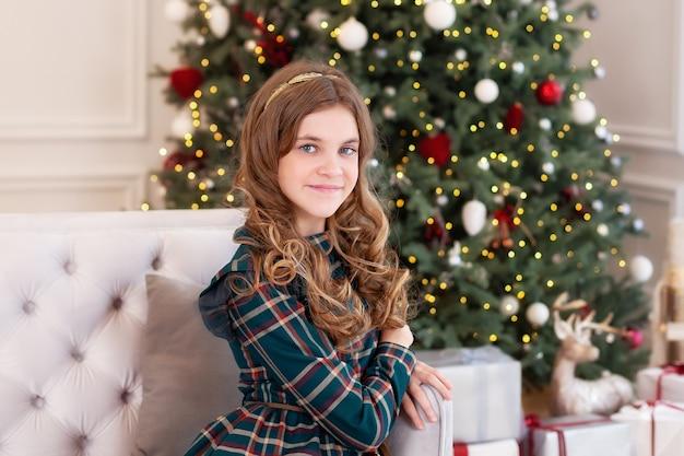 Petite fille souriante près de l'arbre de noël