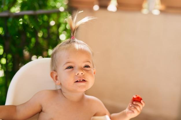 Une petite fille souriante avec une queue de cheval est assise sur une chaise haute et tient une fraise dans sa main en gros plan