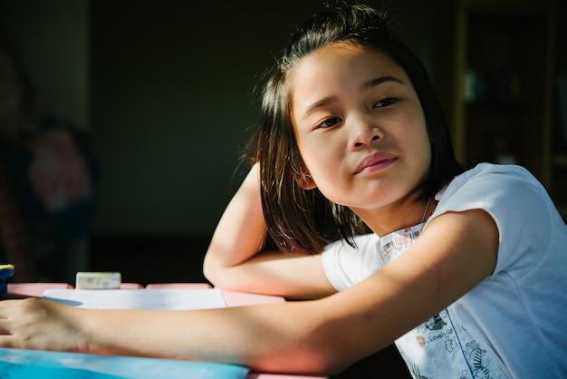 Petite fille souriante et regardant par la fenêtre.