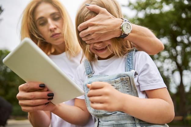 Petite fille souriante avec sa belle mère se reposant dans le parc de la ville au téléphone portable