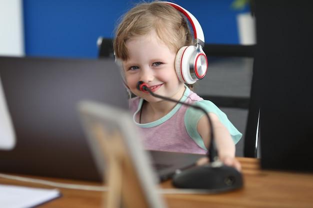 Petite fille souriante à la table de travail avec un ordinateur portable dans les écouteurs se tient à côté du microphone