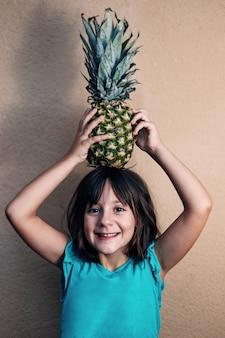 Petite fille souriante, tenant un ananas avec ses mains sur sa tête, concept de l'été