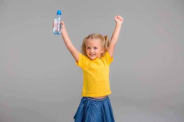 Petite fille souriante tenant une bouteille d'eau