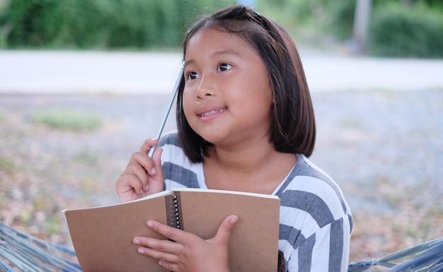 Petite fille souriante et tenant un carnet brun et un crayon dans les mains.