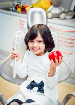 Petite fille souriante, tenant dans les mains une brosse à dents et une pomme.