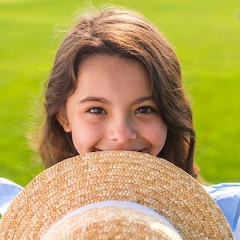 Petite fille souriante tout en tenant son chapeau
