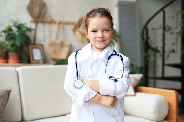 Petite fille souriante en uniforme médical jouant avec un stéthoscope à la maison.