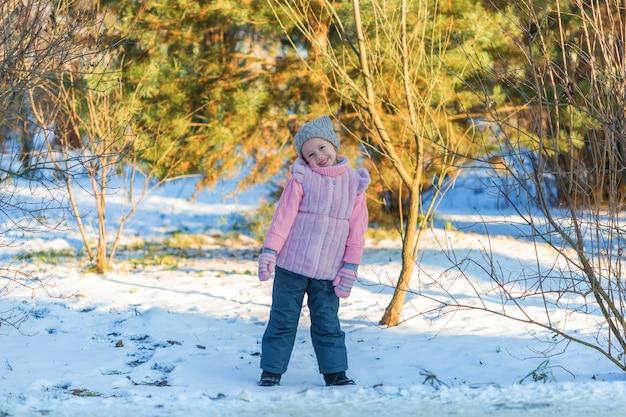 Petite fille sourit dans la forêt d'hiver. enfance heureuse. enfants à l'extérieur concept de vacances d'hiver amusant